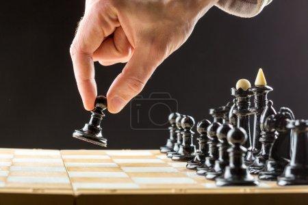 man's hand playing chess