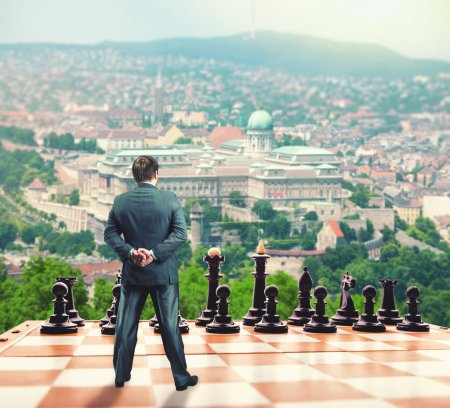 Businessman standing on the chess board