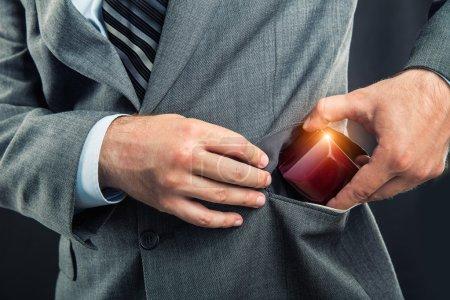 Mettre une boîte-cadeau dans la poche de l'homme