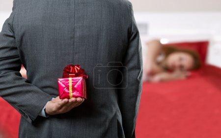 Homme avec un cadeau derrière son dos
