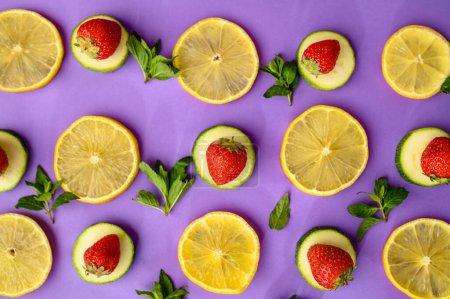 Photo for Fresh lemon slices and strawberries on purple background. Organic vegetarian food, grocery assortment, natural eco products, healthy lifestyle concept - Royalty Free Image