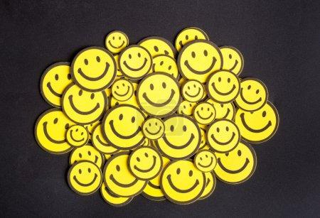 Photo pour Sourire des visages jaunes sur fond noir - image libre de droit