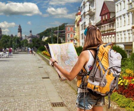 Photo pour Jolie voyageuse avec sac à dos dans une ville européenne lit une carte - image libre de droit