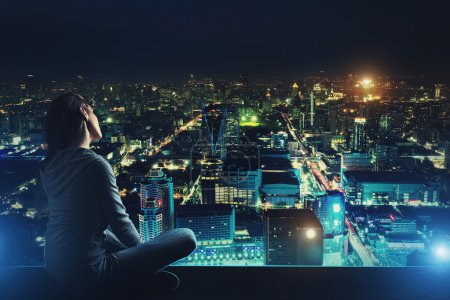 Photo for Pensive woman is sitting on the roof and looking at night city - Royalty Free Image