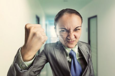 Photo for Angry irritated woman clenching her fist in the office - Royalty Free Image