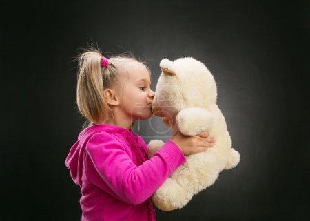 Photo pour Petite fille mignonne baisers jouet ours sur gris - image libre de droit