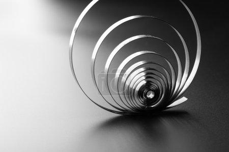 Photo pour Ressort métallique abstrait sur fond gris - image libre de droit
