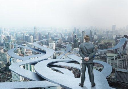Photo pour Homme d'affaires est debout en choisissant son chemin sur fond de ville - image libre de droit