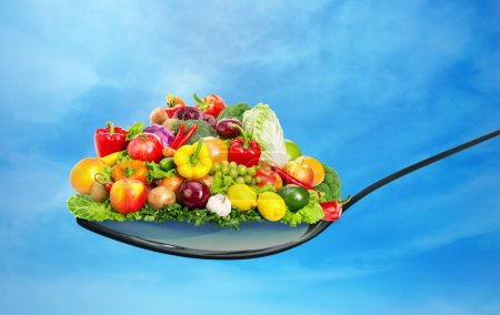Photo for Spoon full of various fruit and vegetables on blue sky - Royalty Free Image