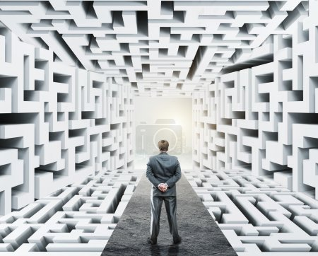 Businessman standing surrounded by labyrinth