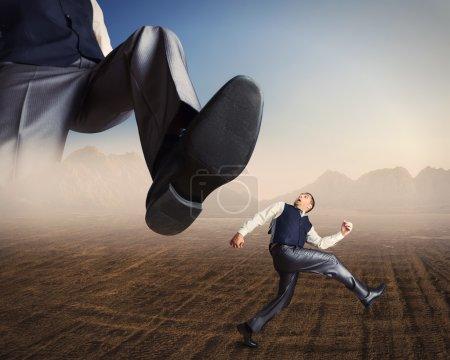 Businessman runs from a big foot