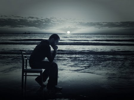 Photo for Man sitting on the chair on the coast at night - Royalty Free Image