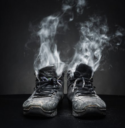 Photo for Old black work shoes from which the smoke proceeds on black background - Royalty Free Image