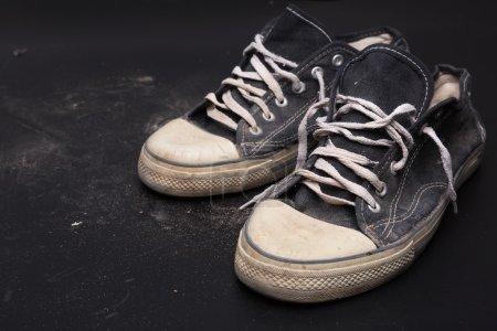 Photo pour Vieux entraîneurs de sport sur le sol sur fond noir. Illustration - image libre de droit
