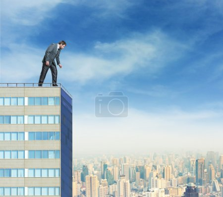 Businessman looks down from  building