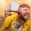 Strange man in a terry bathrobe is cleaning his ear by a plunger in his ear in home interior