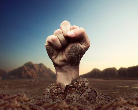 Human fist bursts through the ground