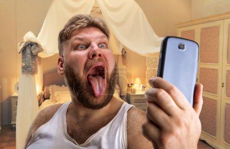 Photo pour Adulte homme avec barbe prend selfie montrant sa langue dans la chambre à coucher - image libre de droit