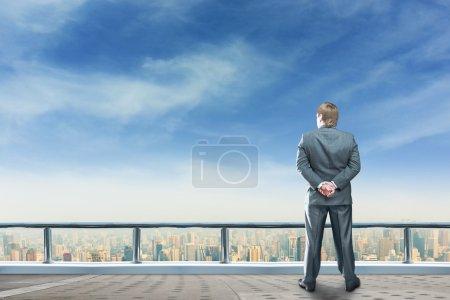 Businessman on top of skyscraper