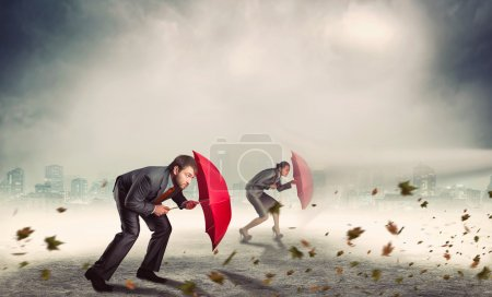 Businessman and businesswoman with umbrellas in storm