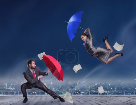 Business people fighting with umbrellas