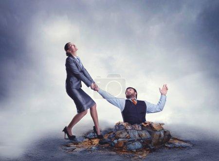 Businesswoman helps businessman