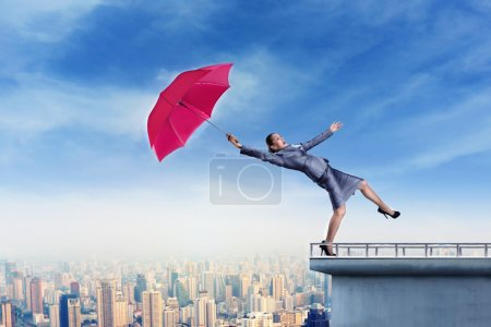 Photo for Scared businessman  with umbrella is falling from the edge of the building by wind blow - Royalty Free Image