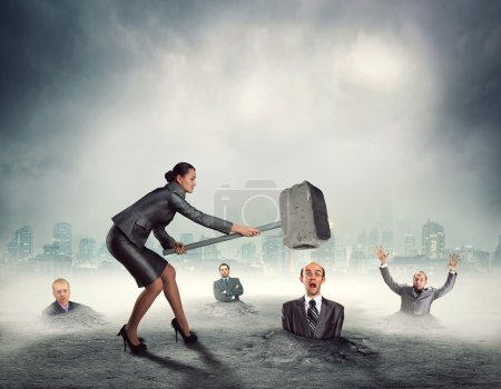 Businesswoman with sledgehammer banging workers