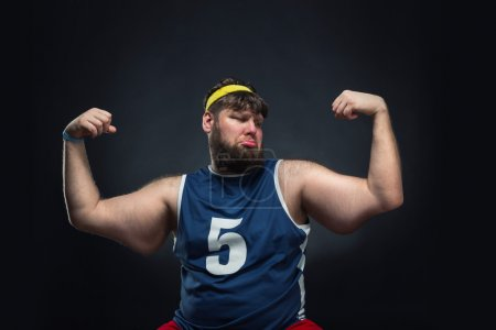 Fat man shows muscles