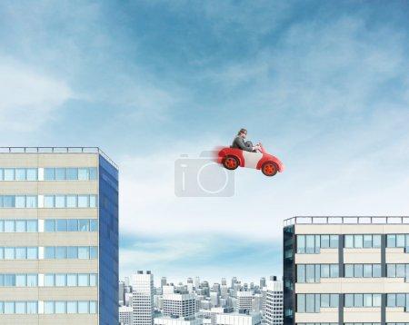 Photo pour Jeune homme d'affaires conduisant une voiture jouet et sautant entre deux bâtiments - image libre de droit