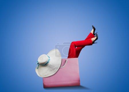 Photo pour Femme assise dans un grand sac à provisions - image libre de droit