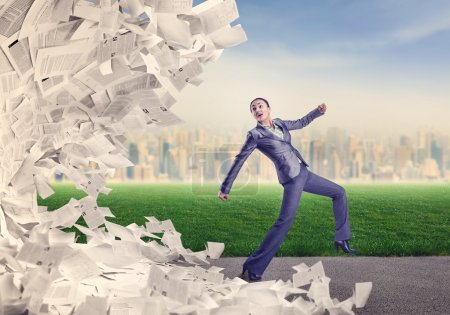 Businesswoman running from papers