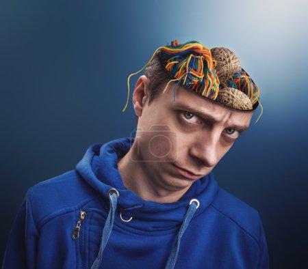 Photo pour Jeune homme avec des boules de fils au lieu de son cerveau - image libre de droit