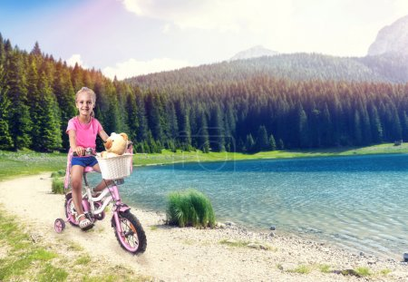 Photo for Cute little girl cycling on pink bike near the lake - Royalty Free Image
