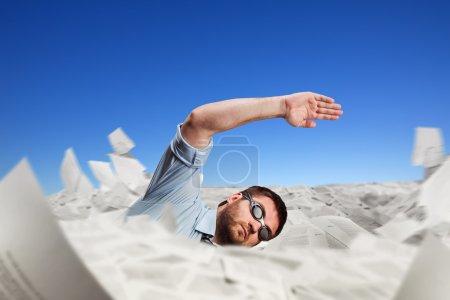 Photo pour Homme dans googles nager dans les papiers - image libre de droit