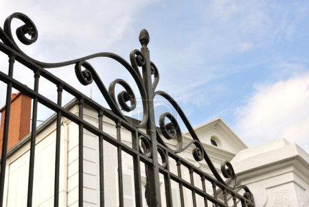 Photo for Details of a black wrought iron gate in front of house - Royalty Free Image
