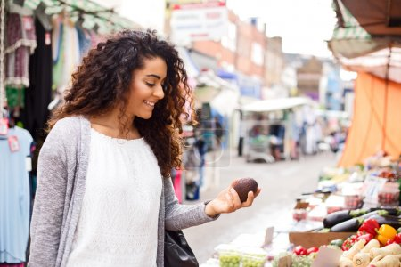 young woman shopping for food at a street market