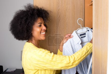 Photo for A young woman at home taking a shirt out of a wardrobe for her man. - Royalty Free Image