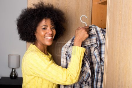 Photo for Young woman taking a shirt out of a wardrobe - Royalty Free Image
