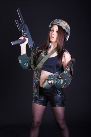 Beautiful young woman in a military uniform with a submachine gu
