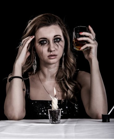 Photo for Depressed young woman with a glass of whiskey over black background - Royalty Free Image