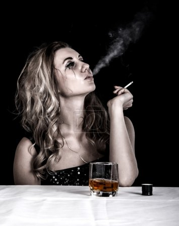 Photo for Depressed young woman with a glass of whiskey and a cigarette over black background - Royalty Free Image