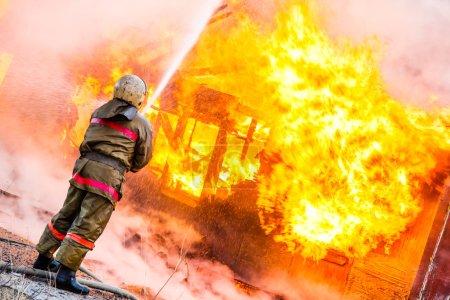 Photo pour Un pompier éteint un incendie dans une vieille maison en bois - image libre de droit