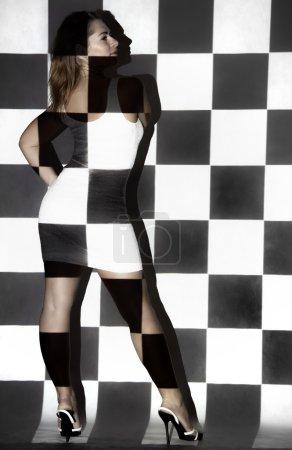 Photo pour Belle jeune femme couverte de petits carrés noirs et blancs - image libre de droit
