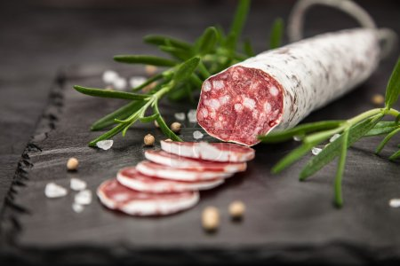 Traditional italian salami on dark background...