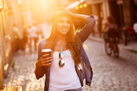 Photo pour Jeune femme élégante de boire du café pour aller dans une rue de ville - image libre de droit