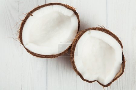 Cracked coconut on wooden table