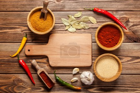 Bowls with spices on wood