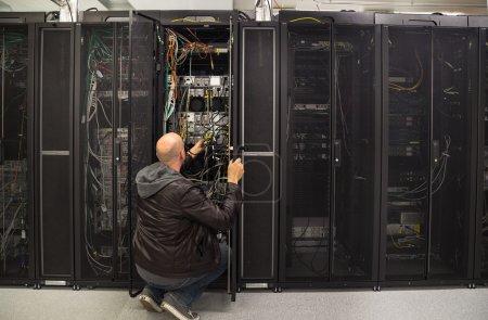 Photo pour Administrateur réseau travaillant sur un problème dans une salle de serveurs - image libre de droit