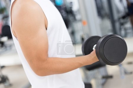 Yound man working out in mdoern gym